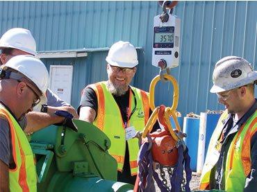 Personal pesando equipos en una báscula de grúa